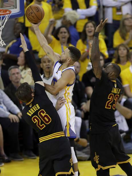 Golden State Warriors guard Stephen Curry shoots between Cleveland Cavaliers guard Kyle Korver (26) and forward LeBron James (23) during the second half of Game 5 of basketball's NBA Finals in Oakland, Calif., Monday, June 12, 2017. (AP Photo/Marcio Jose Sanchez)