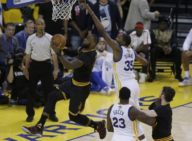Cleveland Cavaliers forward LeBron James, left, shoots against Golden State Warriors forward Kevin Durant (35) during the second half of Game 5 of basketball's NBA Finals in Oakland, Calif., Monday, June 12, 2017. (AP Photo/Ben Margot)