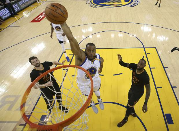 Golden State Warriors forward Andre Iguodala (9) dunks between Cleveland Cavaliers forward Kevin Love (0) and forward LeBron James (23) during the first half of Game 5 of basketball's NBA Finals in Oakland, Calif., Monday, June 12, 2017. (Ezra Shaw/Pool Photo via AP)