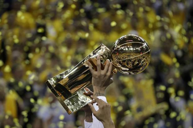 Golden State Warriors center JaVale McGee holds up the Larry O'Brien NBA Championship Trophy after Game 5 of basketball's NBA Finals between the Warriors and the Cleveland Cavaliers in Oakland, Calif., Monday, June 12, 2017. The Warriors won 129-120 to win the NBA championship. (AP Photo/Marcio Jose Sanchez)