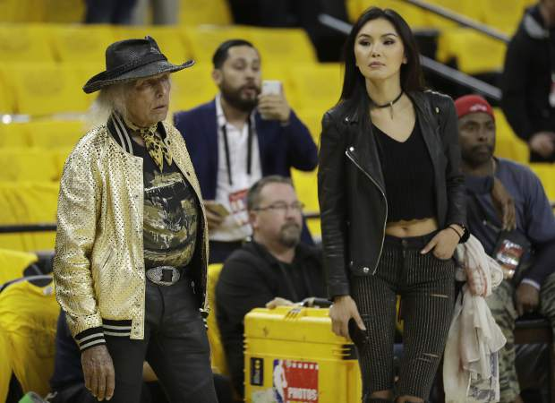 Basketball fan Jimmy Goldstein, left, watches as players warm up before Game 5 of basketball's NBA Finals between the Golden State Warriors and the Cleveland Cavaliers in Oakland, Calif., Monday, June 12, 2017. (AP Photo/Marcio Jose Sanchez)