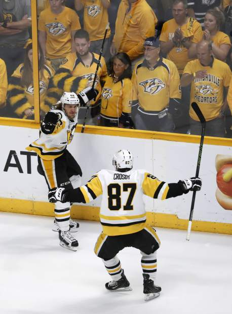 Pittsburgh Penguins' Carl Hagelin (62), of Sweden, celebrates with Sidney Crosby (87) after scoring a goal against the Nashville Predators during the third period of Game 6 of the NHL hockey Stanley Cup Final, Sunday, June 11, 2017, in Nashville, Tenn. (AP Photo/Jeff Roberson)