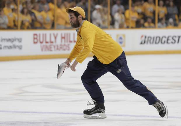 A worker removes a catfish thrown onto the ice after a Nashville Predators goal against the Pittsburgh Penguins during the third period in Game 3 of the NHL hockey Stanley Cup Finals Saturday, June 3, 2017, in Nashville, Tenn. (AP Photo/Mark Humphrey)