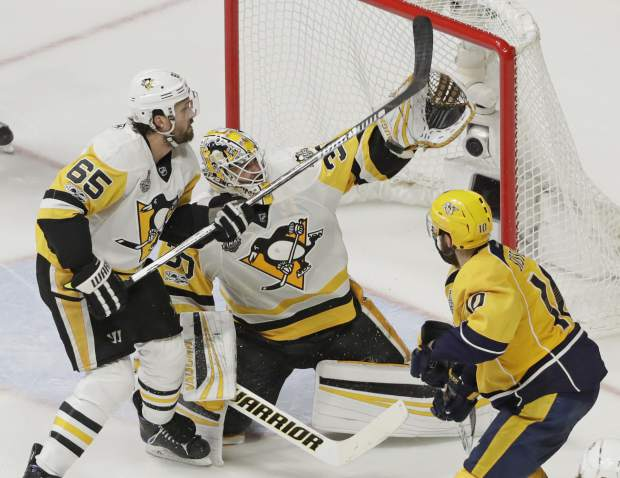 Pittsburgh Penguins goalie Matt Murray (30) and defenseman Ron Hainsey (65) stop a shot by Nashville Predators' Colton Sissons (10) during the third period in Game 4 of the NHL hockey Stanley Cup Finals Monday, June 5, 2017, in Nashville, Tenn. (AP Photo/Mark Humphrey)