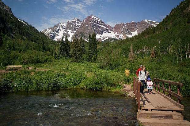 A family walks on the wild side at Maroon Lake Wednesday. The area is a gateway to the Maroon Bells-Snowmass Wilderness, just behind the sign in the center.