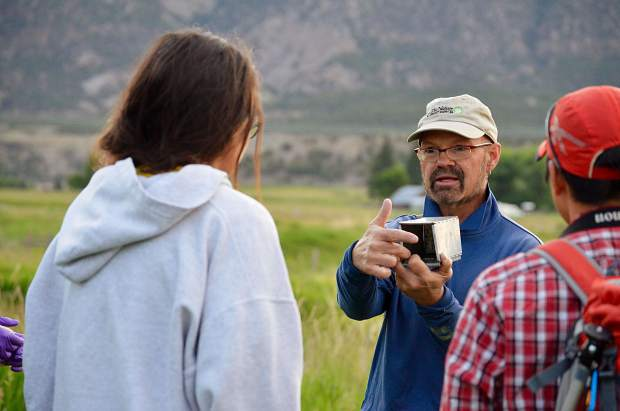 John Sovell, a zoologist and ecologist with the Colorado Natural Heritage Program, demonstrates for student interns how the small traps operate and how to retrieve an animal from inside.