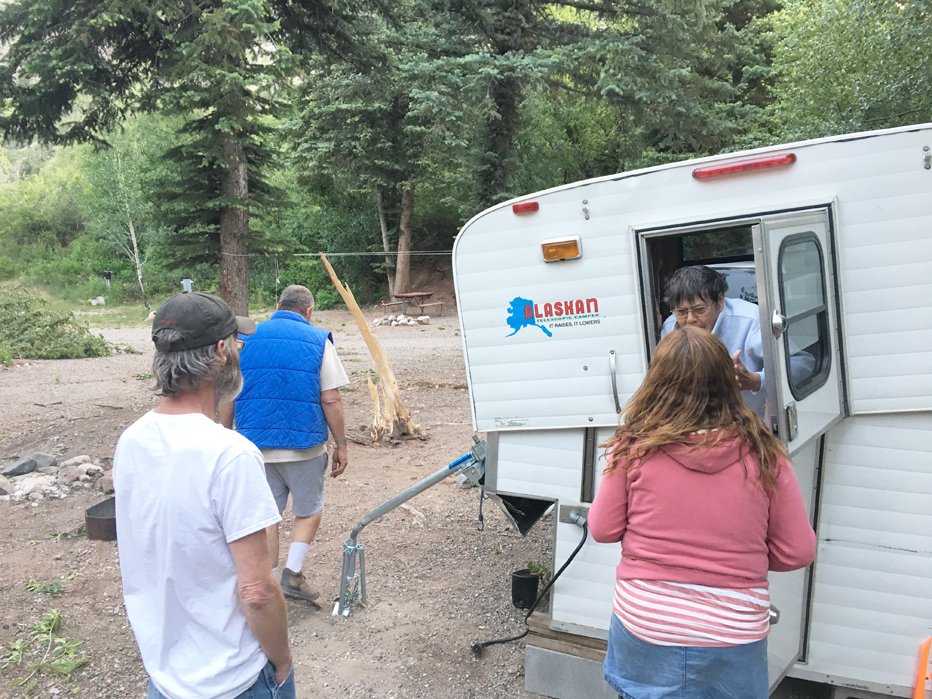 Neighboring campers help Betty and Al Whetherbee out of their camper after nearly being crushed by a fallen tree.