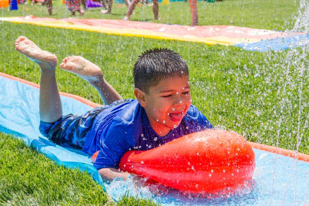 Tony De La Fuente, 5, rolls down the slip-n-slide at the Glenwood Springs Community Center H2O Day. Kids of all ages were invited to have fun in the sun and cool off in the multiple water features Wednesday afternoon. For more photos from the event, visit postindependent.com.