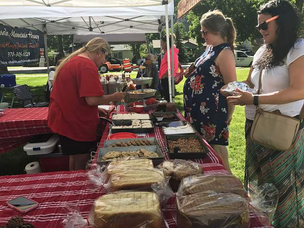 Holly Pihl serves customers at her Gluten Free Momma tent. She said the early crowd at the inaugural Glenwood Market was smaller than average, but that many people miss the first week of any market because they didn't know it started.