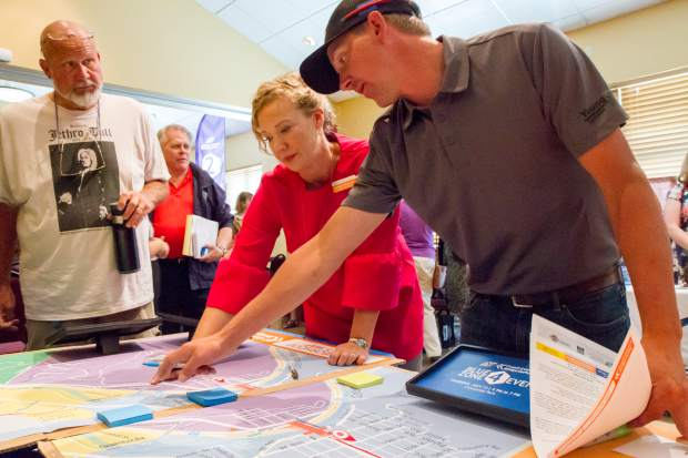 Kathleen Wanatowicz with the Grand Avenue Bridge Project explains a detour map to Daniel Jurmu during the Open House Community Meeting on Tuesday morning.