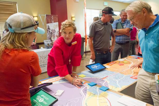 Kathleen Wanatowicz speaks with members of the public about the bridge detour during the Open House Community Meeting on Tuesday morning.