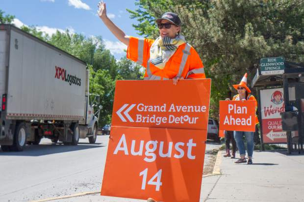 Public Information Manager for the Grand Avenue Bridge Project Kathleen Wanatowicz and other PR members hold informational signs at 11th and Grand Avenue on Wednesday afternoon. The detour is just under two months out and motorists are urged to begin plannnig how they are going to help in ways to ease traffic congestion during the bridge closure.