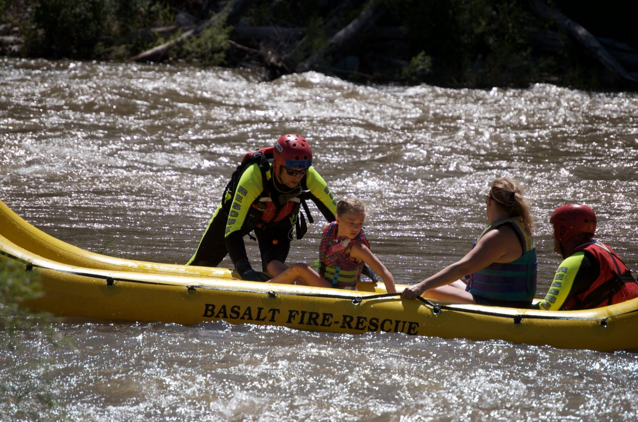 A swift water rescuer gets a young girl and a woman ready to ferry through heavy current.