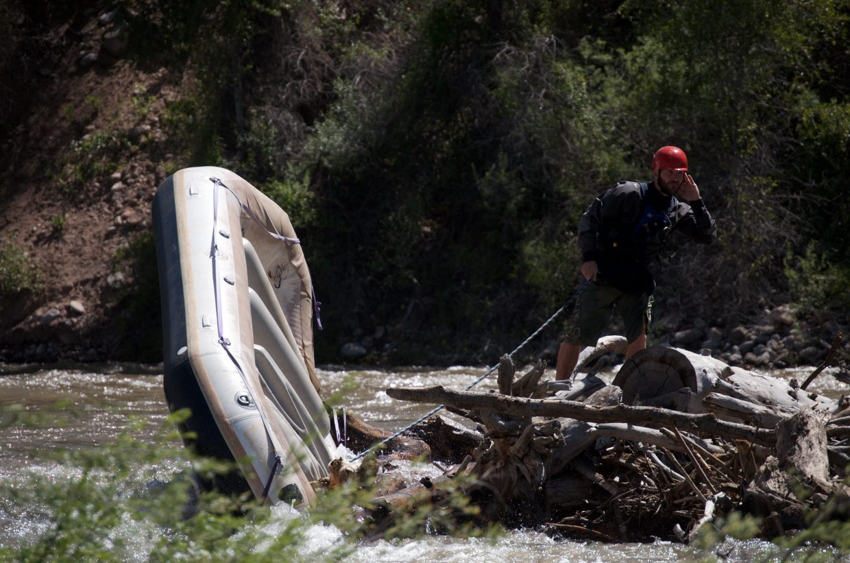 A swift water rescuer keeps tabs on the pinned raft after the family was successfully retrieved.