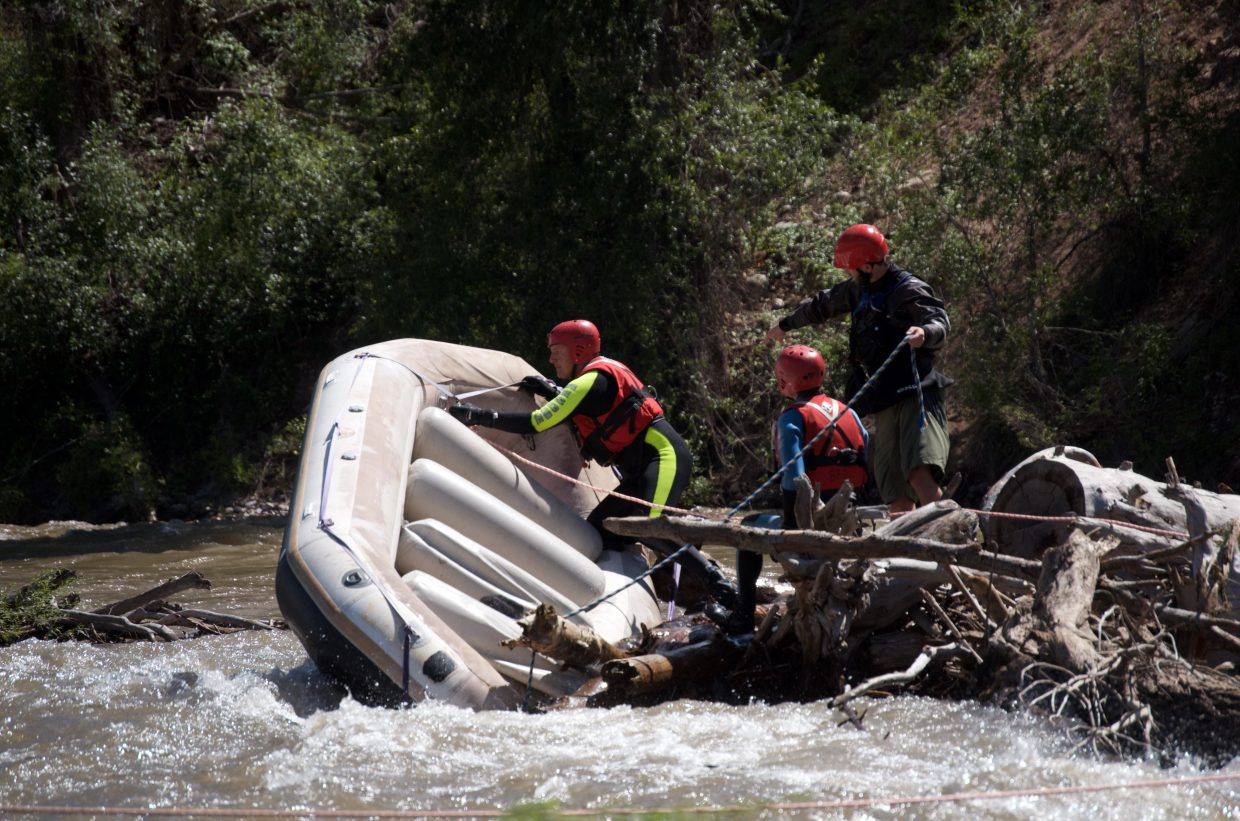 Swift water rescuers work to dislodge a raft pinned in a logjam on the Roaring Fork River Monday.