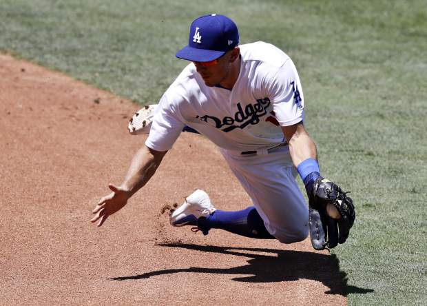 Los Angeles Dodgers second baseman Austin Barnes fields a ball hit by Colorado Rockies' Charlie Blackmon during the second inning of a baseball game in Los Angeles, Sunday, June 25, 2017. Blackmon was out at first. (AP Photo/Chris Carlson)