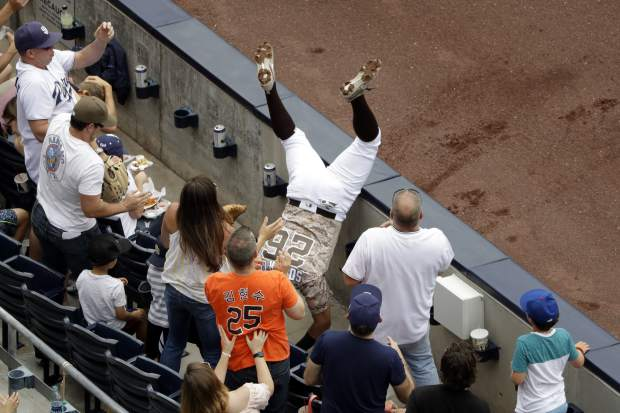 San Diego Padres second baseman Yangervis Solarte falls into the seats chasing a foul ball hit by the Colorado Rockies' Jeff Hoffman during the fourth inning of a baseball game, Sunday, June 4, 2017, in San Diego. (AP Photo/Gregory Bull)