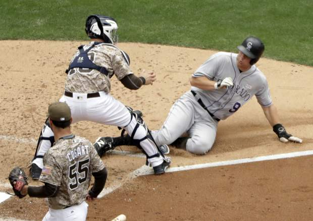 Colorado Rockies' DJ LeMahieu, right, slides in late to home and is tagged out by San Diego Padres catcher Austin Hedges during the fourth inning of a baseball game Sunday, June 4, 2017, in San Diego. (AP Photo/Gregory Bull)