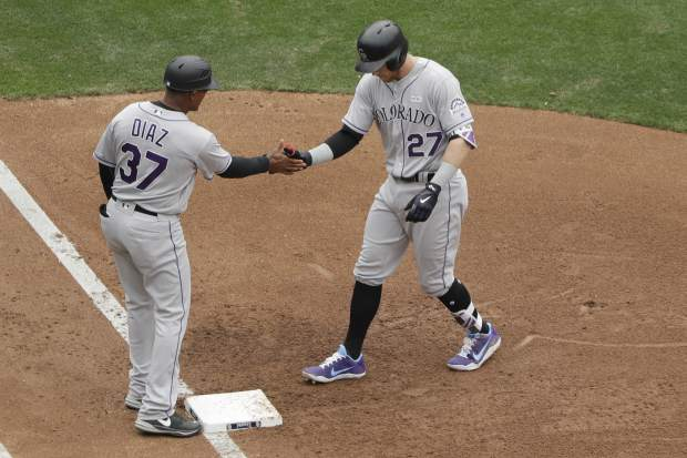Colorado Rockies' Trevor Story (27) is greeted by first base coach Tony Diaz (37) after hitting a two-RBI single during the fourth inning of a baseball game against the San Diego Padres, Sunday, June 4, 2017, in San Diego. (AP Photo/Gregory Bull)