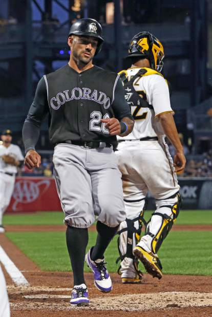 Colorado Rockies' Ian Desmond, left, scores on a single by Rockies' Trevor Story off Pittsburgh Pirates relief pitcher Wade LeBlanc in the sixth inning of a baseball game in Pittsburgh, Monday, June 12, 2017. (AP Photo/Gene J. Puskar)