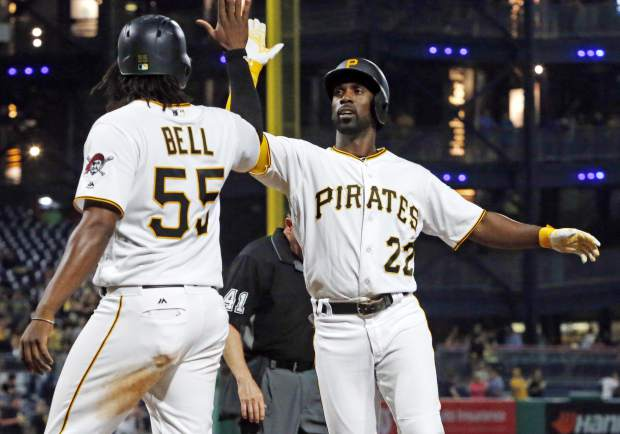 Pittsburgh Pirates' Andrew McCutchen (22) celebrates with Josh Bell (55) who was on base for his two-run home run off Colorado Rockies relief pitcher Jordan Lyles in the eighth inning of a baseball game in Pittsburgh, Tuesday, June 13, 2017. It was McCutchen's second homer of the game. The Pirates won 5-2. (AP Photo/Gene J. Puskar)