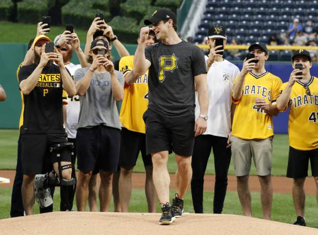 Pittsburgh Penguins captain Sidney Crosby reacts after throwing out a ceremonial first pitch, as his teammates record the occasion, before a baseball game between the Pittsburgh Pirates and the Colorado Rockies in Pittsburgh, Tuesday, June 13, 2017. The Penguins were on hand to celebrate their Stanley Cup win over the Nashville Predators. (AP Photo/Gene J. Puskar)