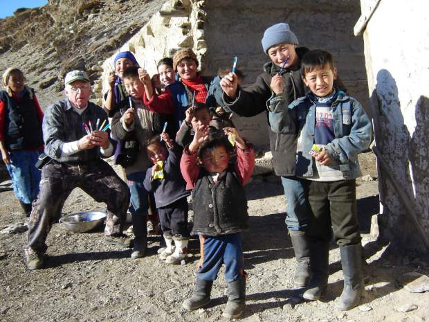 Bill Slattery hands out crayons and coloring books to the village children after one of his sheep hunts in Mongolia.