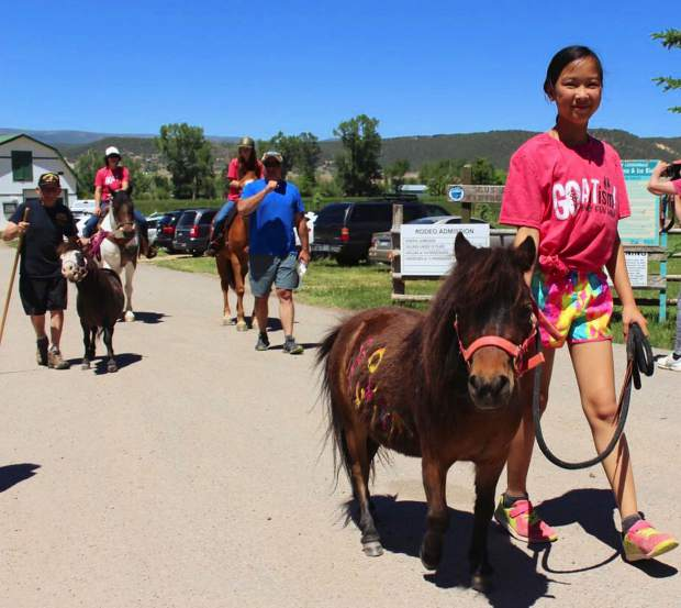 Maeve Doubleday, 10, of Glenwood Springs, walks Lakoda, a mini horse, at the Go AuTism Family Fun Walk, an annual fundraiser for Smiling Goat Ranch in Carbondale. Established in 2015, the nonprofit organization helps children with autism and veterans with PTSD free of charge by using the healing effects of horses, movement, nature and supportive community. Lt. Col. Dick Merritt, left, walks Dakini, another mini horse, and next to them is Chief Paul Nunemann, the JROTC instructor at Glenwood Springs High School.