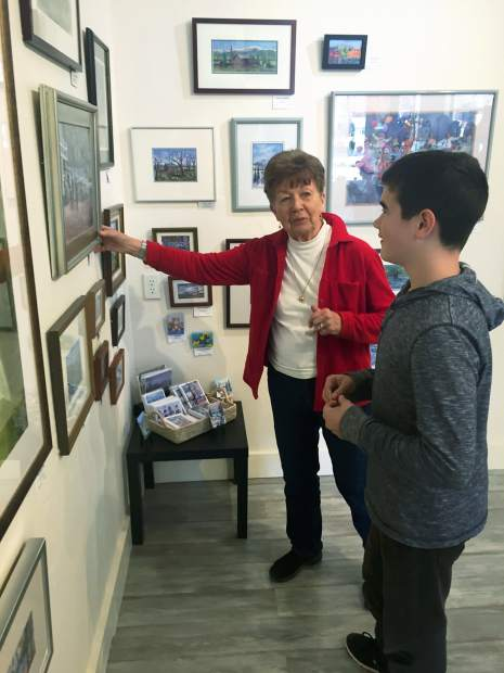 Law explains the subject choice and technique in her artwork to her grandson.