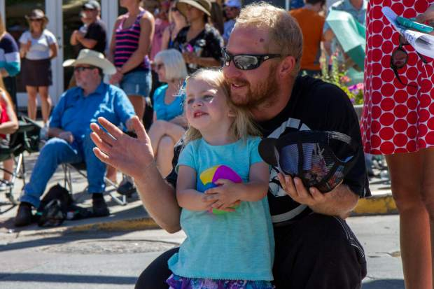 Tezlie Allen, 2, and her dad Kyle wave and watch the 2017 Strawberry Days Parade. They enjoy the parade and festival every year.