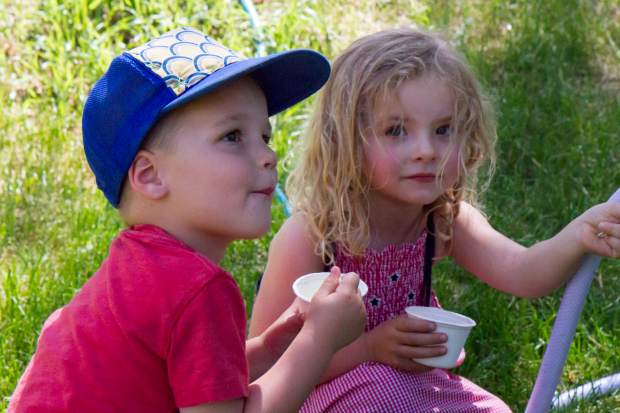 Three-year-olds River Smith and Ellie Golden enjoy their free strawberries and ice cream in the park after the parade.
