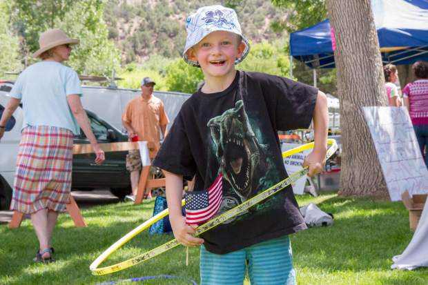 Gunnison Colson, 6, tries out his hula-hooping skills in the park after the Strawberry Days Parade on Saturday morning.