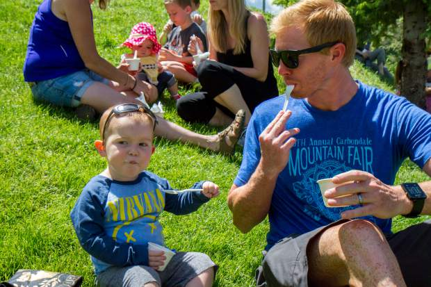 Rainer Anthon, 2, and his dad Ryan relax in the park with their free strawberries and ice cream after the parade on Saturday morning. This is Rainer's third year enjoying Strawberry Days; he spent his first time in the park when he was only a couple of weeks old.