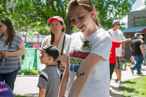 Lindsay Juhl (13) checks out her new tattoo at the face painting station in the park during the 2017 Strawberry Days.