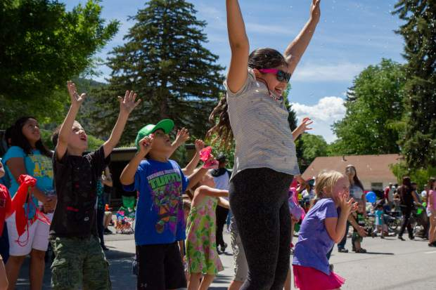 Excited kids enjoy being sprayed with water on a hot Saturday morning during the 2017 Strawberry Days Parade.