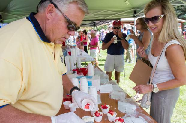 Festival goers enjoy free strawberries and ice cream in the park after the parade on Saturday morning.