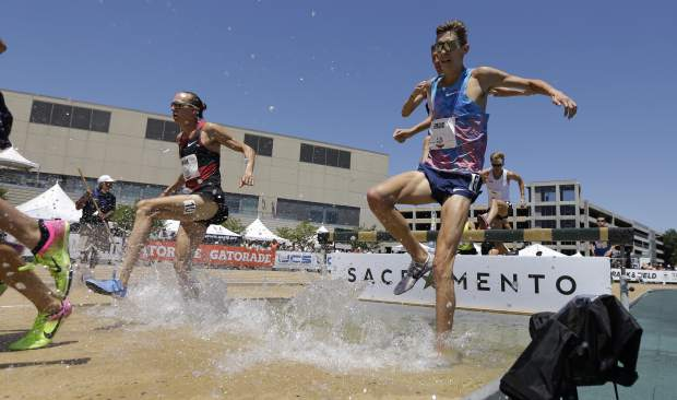 Evan Jager, left, runs with Mason Ferlic, right, through the water in the men's 3000-meter steeplechase at the U.S. Track and Field Championships, Sunday, June 25, 2017, in Sacramento, Calif. Jager won the event. (AP Photo/Rich Pedroncelli)