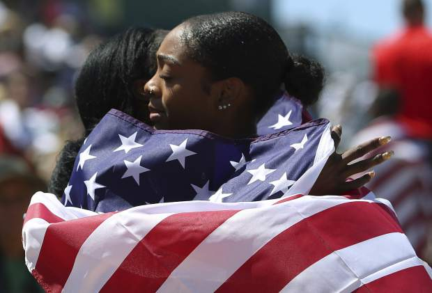 Deajah Stevens, right, hugs Kimberlyn Duncan, left, as they hold U.S. flags after Stevens placed first and Duncan placed second in the women's 200 meters at the U.S. Track and Field Championships, Sunday, June 25, 2017, in Sacramento, Calif. (AP Photo/Rich Pedroncelli)