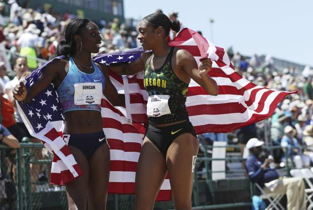 Deajah Stevens, right, moves to hug Kimberlyn Duncan, left, as they hold United States flags after Stevens placed first and Duncan placed second in the women's 200 meters at the U.S. Track and Field Championships, Sunday, June 25, 2017, in Sacramento, Calif. (AP Photo/Rich Pedroncelli)