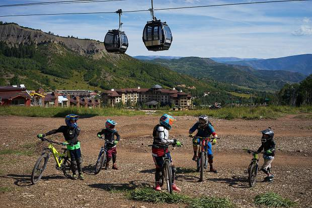 An instructor takes a break to explain maneuvers to a group of young students at the Snowmass bike park last August.
