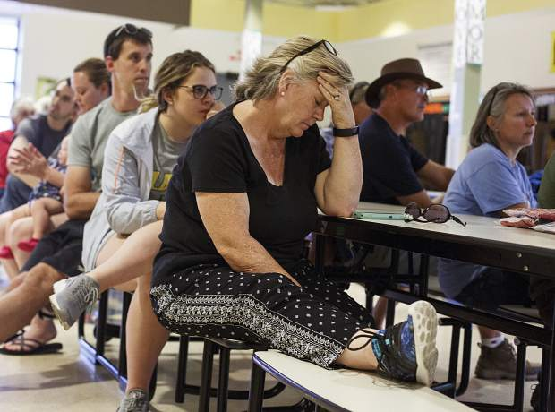 Breckenridge resident, Sheila Calhoun, who evacuated her home due to Peak 2 fire, rests her head during a briefing inside Summit Middle School lobby Wednesday, July 5 in Frisco.