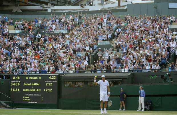 Spectators do a wave as Luxembourg's Gilles Muller prepares to serve to Spain's Rafael Nadal during their Men's Singles Match on day seven at the Wimbledon Tennis Championships in London Monday, July 10, 2017. (AP Photo/Tim Ireland)