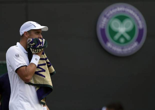 Luxembourg's Gilles Muller wipes his face as he plays Spain's Rafael Nadal during their Men's Singles Match on day seven at the Wimbledon Tennis Championships in London Monday, July 10, 2017. (AP Photo/Tim Ireland)