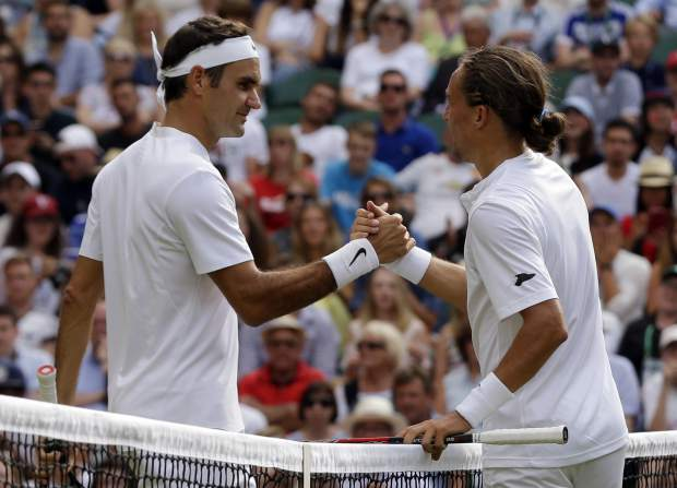Roger Federer, left, shakes hands with Alexandr Dolgopolov after their match Tuesday.