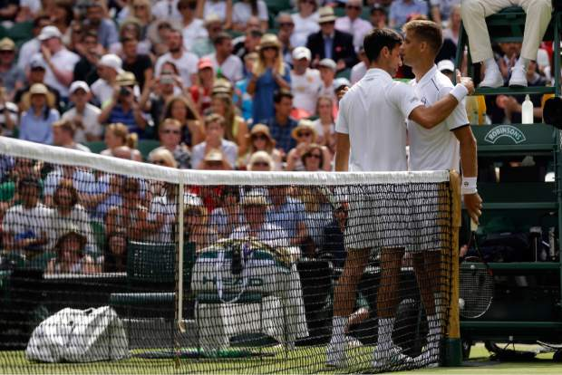 Novak Djokovic, left, embraces Martin Klizan after their match Tuesday at Wimbledon.