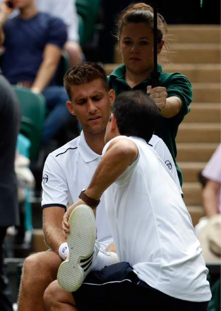 Slovakia's Martin Klizan receives medical attention during his Men's Singles Match against Serbia's Novak Djokovic on day two at the Wimbledon Tennis Championships in London Tuesday, July 4, 2017. (AP Photo/Alastair Grant)