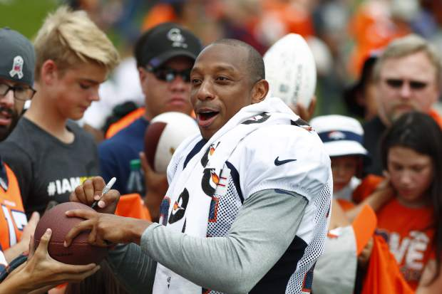 Denver Broncos cornerback Chris Harris gives autographs to fans after drills at NFL football training camp Sunday, July 30, 2017, in Englewood, Colo. (AP Photo/David Zalubowski)