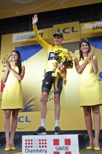 Britain's Chris Froome, wearing the overall leader's yellow jersey, celebrates on the podium after the ninth stage of the Tour de France cycling race over 181.5 kilometers (112.8 miles) with start in Nantua and finish in Chambery, France, Sunday, July 9, 2017. (AP Photo/Christophe Ena)