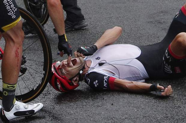A screaming Manuele Mori of Italy lies on the road after crashing during the ninth stage of the Tour de France cycling race over 181.5 kilometers (112.8 miles) with start in Nantua and finish in Chambery, France, Sunday, July 9, 2017. Mori's injury forced him to abandon the race. (AP Photo/Christophe Ena)