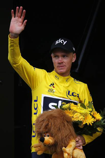 Britain's Chris Froome, wearing the overall leader's yellow jersey, waves on the podium after the eighth stage of the Tour de France cycling race over 187.5 kilometers (116.5 miles) with start in Dole and finish in Station des Rousses, France, Saturday, July 8, 2017. (AP Photo/Peter Dejong)